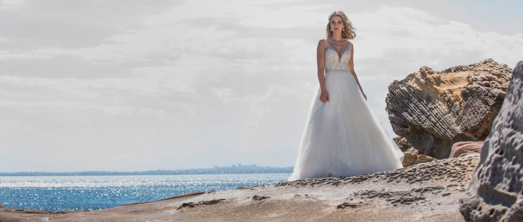 Beautiful bride in her wedding dress beside the sea